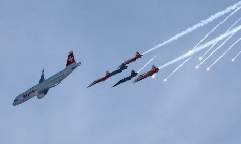 Members of the Swiss aerobatic team Patrouille Swiss fly in formation with a Swiss Airbus A 320 in Wengen